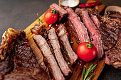 grilled beef steaks, different roasts on a stone background