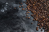 Roasted coffee beans on rustic table. Black background. Top view. Copy space