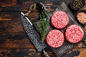 Raw steak burgers patties with ground beef and thyme on a wooden cutting board. Dark Wooden background. Top view. Copy space