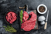 Beef fillet round cut Sliced on a butcher cutting board. Black background. Top view