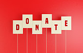 Donate Writes on White Tag Over Red Background.
