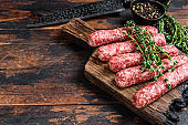 Homamade raw meat lula kebabs sausages on a cutting board. Dark wooden background. Top view. Copy space