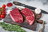Raw denver cut black angus organic steak on a butcher cutting board with herbs. White background. Top view