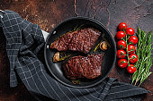 Grilled denver beef meat steak in a pan with rosemary. Dark background. Top view