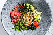 Poke bowl with raw tuna fish and vegetables. Hawaiian dish. Healthy eating concept. Gray background. Top view