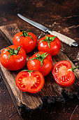Cut Red cherry tomatoes on wooden cutting  board. Dark background. Top view
