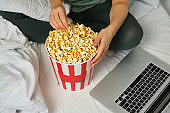 Popcorn bucket in the hands of a young girl preparing to watch a movie in bed on the laptop. Showtime. Eating delicious unhealthy sweet snacks. Watching new film in home. Rest and entertainment in bedroom. Popcorn closeup