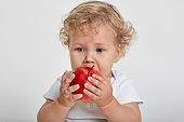 Baby with apple posing isolated over white background, blond tot biting red fruit and looking away, vitamins for male kid, wavy haired child having snack.