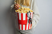 Popcorn paper bucket and 3D glasses in the hands of a young girl preparing to watch a movie. Showtime. Eating delicious unhealthy sweet snacks. Going to cinema for a new film. Rest and entertainment. Popcorn closeup