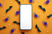 Flat lay Halloween phone mockup blank screen on a paper bats and spiders background in 3D rendering. Happy Halloween mobile phone banner template