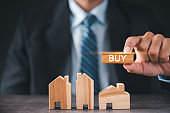 Businessman holding a wooden block, the word for buy, with three wooden block houses in front. Buy-sell investment concept Real estate business.