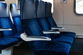 Close up image of blue armchairs in empty train in row of three, no people in wagon,