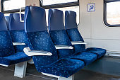Blue armchairs in empty train in row of three, no people in wagon,