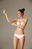 Woman pinching skin on her hand checking subcutaneous body fat layer