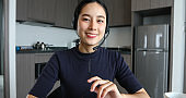 Asian women wearing headphone and using digital tablet video Conference and meeting and drinking coffee in The kitchen at the home