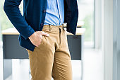 Close up fashion image of wrist in a business suit of man detail of a businessman,Man's hand in brown or gold pants pocket and wearing blue jacket and blue shirt In the office room background.