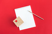 Notebook with blank page, pencil and gift box on a red background.