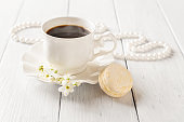 One beige macaroon and cup of hot coffee against pearl beads on a white wood table. Sweet breakfast with delicious french dessert. Valentine's day greeting card. High key image. Selective focus.