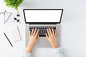 Overhead shot of young female hands working on laptop with empty screen on white desk. Business background with accessories. Flat lay
