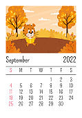 Design template.Calendar for 2022, September. A cute cartoon tiger is sitting under a tree reading a book. Autumn landscape. The symbol of the year. Animal character. Color vector illustration.