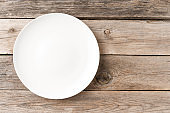 Overhead shot of blank white plate on rustic wooden background. Flat lay