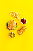 Fast food flat lay set. Burger with fried potatoes and chicken, top view