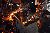 Casting and foundry. Worker in protection suit pouring liquid steel into molds. Metallurgy and steel production.