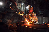 Foundry hardworking people pouring hot liquid iron from bucket into molds. Iron ore production and metallurgy.