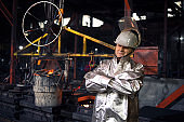 Portrait of workman in aluminized high temperature protection suit with arms crossed standing in foundry steel production factory. In background bucket with liquid molten iron. Metallurgy and heavy industry.
