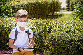 One pupil boy wearing mask is sitting on bench near his school during covid-19 pandemic time. New normal and education concept of coronavirus epidemic