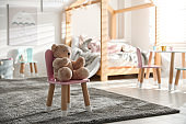 Cute chair with bunny ears and teddy bear in children's bedroom interior