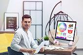 Professional male designer working at desk in modern office