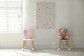 Cute chairs with bunny ears in children's room interior