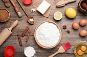 Cooking utensils and ingredients on wooden table, flat lay