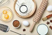 Cooking utensils and ingredients on beige background, flat lay