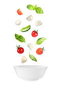 Mozzarella cheese balls, tomatoes and basil leaves falling into bowl on white background. Caprese salad