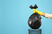 Woman taking garbage bag out of bin on light blue background, closeup. Space for text