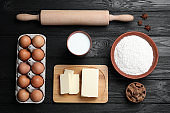 Cooking utensils and ingredients on black wooden table, flat lay