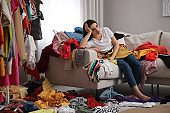 Upset young woman with lots of clothes on sofa in room. Fast fashion