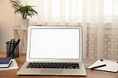 Modern laptop with blank screen on table at home