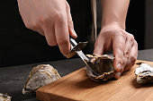 Man opening fresh oyster with knife at grey table, closeup