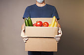 A courier wearing a mask and gloves with box of groceries, safe food delivery