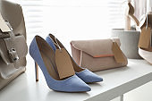 Women's high heel shoes and accessories in modern clothing boutique, space for text