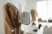 Collection of stylish women's clothes and accessories in modern boutique