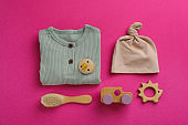 Flat lay composition with baby clothes and accessories on pink background