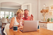 Retired Couple At Home In Kitchen Using Laptop For Video Call With Family