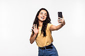 Smiling young woman making selfie photo while waving palm isolated on a white background