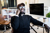 Portrait of african male executive making phone call while sitting in office. Young businessman talking on mobile phone.