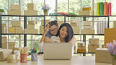 Asian woman and daughter, a family, packing postal parcel packaging carton box delivery, working from home, selling products online business. Shipping service. People lifestyle in coronavirus pandemic