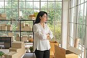 Asian business woman with postal parcel packaging carton box delivery, working from home, selling products online business. Shipping service. People lifestyle in coronavirus pandemic. SME ecommerce